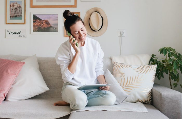 a-young-woman-wearing-white-sweatshirt-and-blue-jeans-is-working-from-home-using-a-mobile-phone
